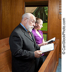 Older Man Young Woman Standing in Church Singing Holding...