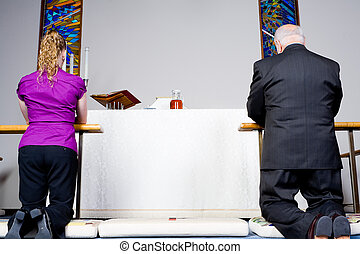 Senior man and young woman kneeling at the communion rail in a church