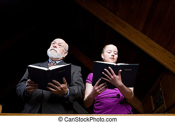 Senior man and young woman stanging, singing, and holding hymnals in church.