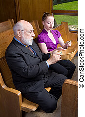 Older man and young woman putting money into an offering basket.  Sitting in a church pew.