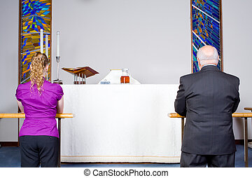 Two Caucasian People Kneeling Taking Communion at Church Alter