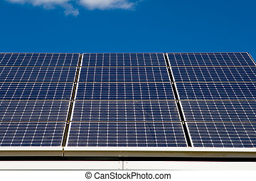 Row of Photovoltaic Solar Panels on Roof Against Blue Sky