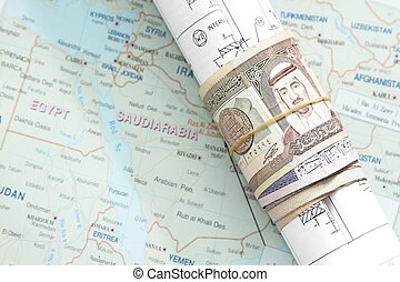 Rolled saudi arabian money in a blueprint in saudi arabia...