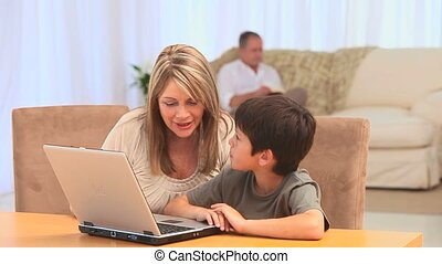 Grandmother and her grandson playing a game on their laptop...