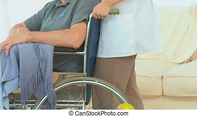 A patient on his wheelchair with his nurse at the hospital