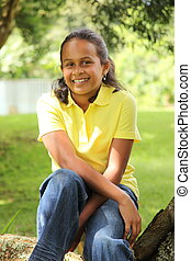 Young girl under a shady tree - Young girl in yellow shirt...