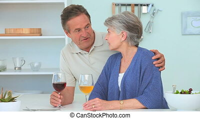 Elderly couple drinking wine in the kitchen