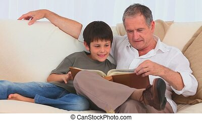 Boy looking at an album with his grandfather on the couch