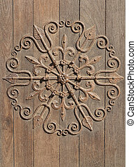 decorative medieval ironwork mounted on an old wooden door