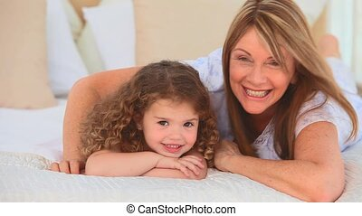 Cute child with her grandmother looking at the camera on the...