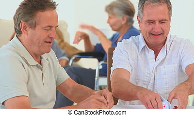 Mature friends playing cards in a nursing home