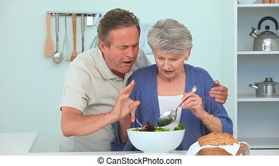 Mature couple preparing a salad in the kitchen