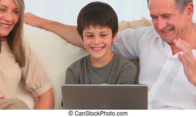 Grandparents and their grandson playing a game on a laptop