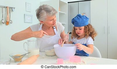 Grandmother and grand daughter baking together in the...