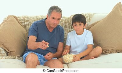 A grandfather with his grandson watching tv in the living...