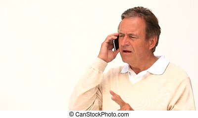 Senior man speaking on the phone isolated on a white...