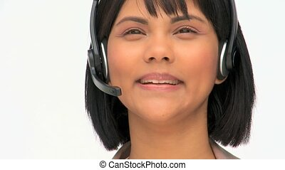 Asian business woman speaking over the headset against a...