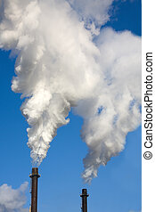 Smoke Stacks - Two chimneys billowing smoke against a blue...