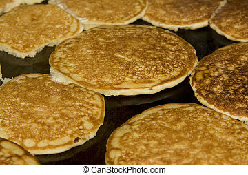 Pancakes - Several pancakes cooking on a griddle