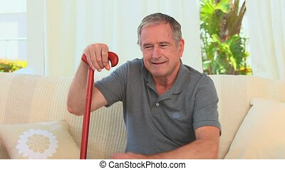 Retired man using a walking stick in his living room