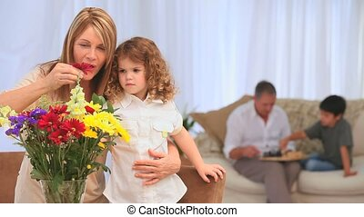 Child smelling flowers with her grandmother in the living...