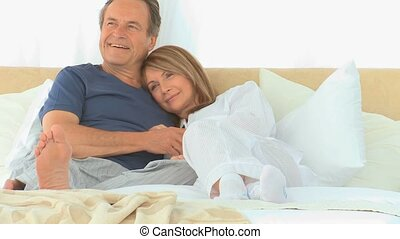 Lovely couple in the bed - Lovely couple watching tv on...