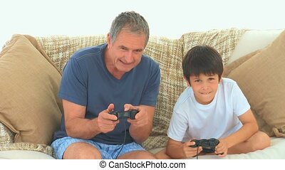 A child playing video games with his grandfather on the sofa