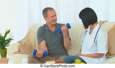 A patient using dumbbells in front of his nurse on his sofa