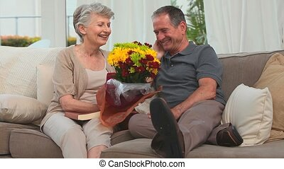 Cute elderly couple with a bunch of flowers