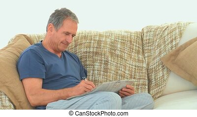 Retired man doing cross words with his newspaper on his...