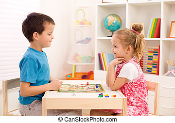 Kids playing board game in their room - Little boy and girl...