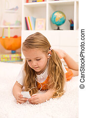 Little girl listening to music laying on the floor