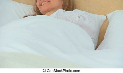 A sick woman laughing in her bed