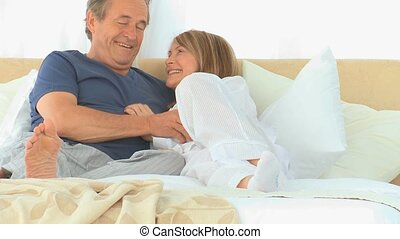 Retired couple talking to each other on their bed