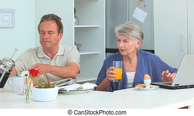 Cute mature couple taking a breakfast in the kitchen