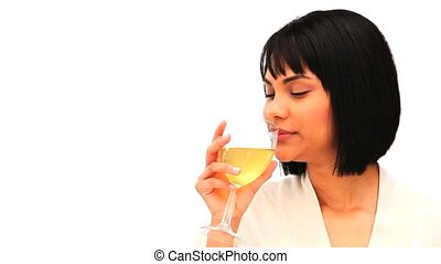 Attractive asian enjoying a glass of white wine against a...