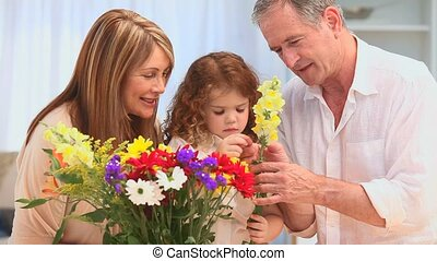 Grandparents making a bunch of flowers with their grand...