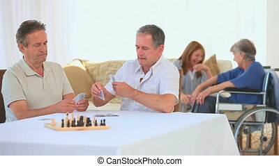 Friendly retired men playing cards in a nursing home