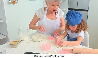 Grandmother baking with her grand daughter in the kitchen