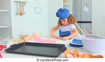 Adorable little girl baking in the kitchen