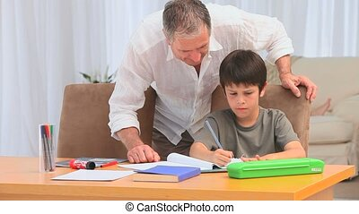 Grandfather helping his grandson to do homeworks in the...