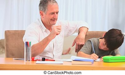 Little boy doing homeworks with his grandfather in the...