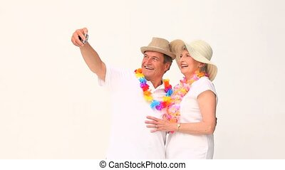 Elderly couple taking a picture of themself isolated on a...