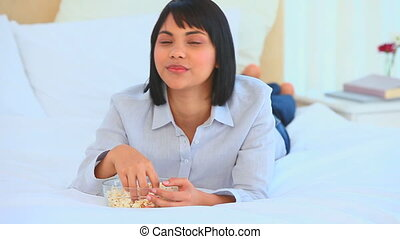 Asian woman on the phone eating popcorn in her bedroom