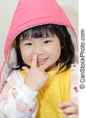 Adorable Asian girl pick her nose, closeup portrait of funny...