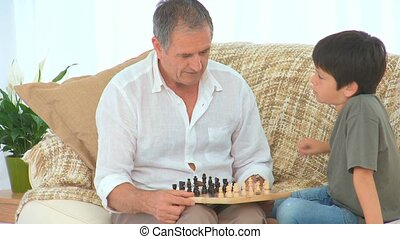 A grandfather teaching to his grandson how to play chess