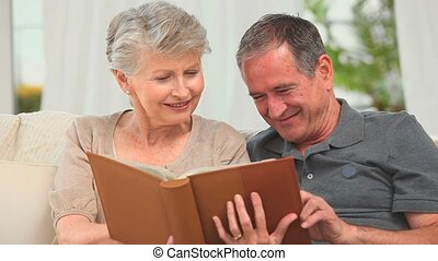 Retired couple looking at an album in the living room