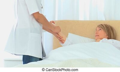 A nurse paying her patient a visit in the bedroom