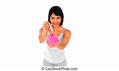 Asian woman saving money on a piggy bank against a white...