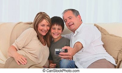 Family taking pictures with a camera in the living room